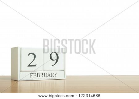 Closeup surface white wooden calendar with black 29 february word on blurred brown wood desk isolated on white background with copy space selective focus at the calendar