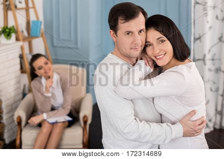 Loving couple. Pleasant delighted nice man standing near his wife and smiling while hugging her