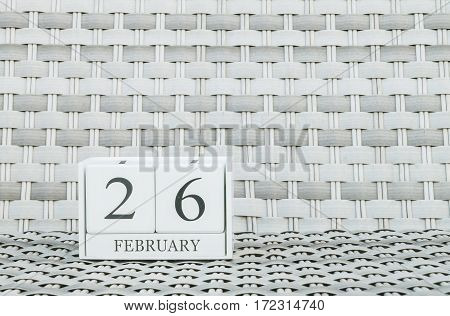 Closeup surface white wooden calendar with black 26 february word on blurred weave wood chair textured background with copy space in selective focus at the calendar