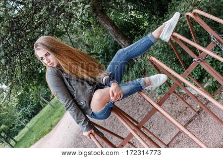 Young Beautiful Teenager Girl Is Sitting On Metal Rods, Bicycle Parking, Rock 'n' Roll. Rock Style.