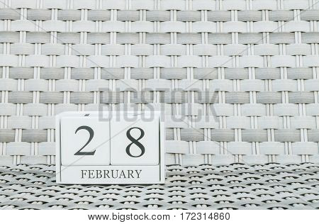 Closeup surface white wooden calendar with black 28 february word on blurred weave wood chair textured background with copy space in selective focus at the calendar