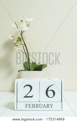 Closeup white wooden calendar with black 26 february word with white orchid flower on white wood desk and cream color wallpaper in room textured background in selective focus at the calendar
