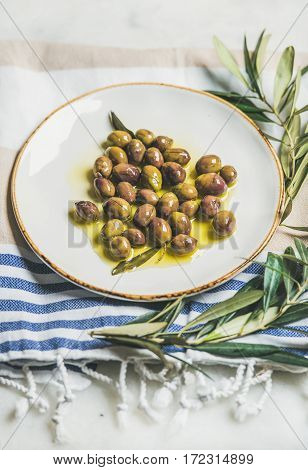 Pickled green Mediterranean olives in natural virgin olive oil on white ceramic plate and olive tree branch on striped towel over grey marble background, selective focus