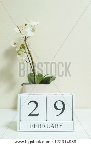 Closeup white wooden calendar with black 29 february word with white orchid flower on white wood desk and cream color wallpaper in room textured background in selective focus at the calendar