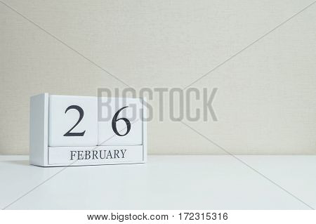 Closeup white wooden calendar with black 26 february word on blurred white wood desk and cream color wallpaper in room textured background with copy space in selective focus at the calendar
