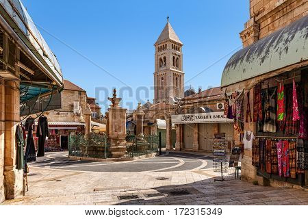 JERUSALEM, ISRAEL - JULY 26, 2015: Small square with fountain and gift shops of Muristan - famous historic complex of streets in Christian Quarter of Old City of Jerusalem, Israel.