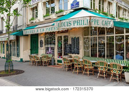 PARIS, FRANCE - MAY 24, 2016: Sidewalk and cafe Louis Philippe - famous parisian bistro since 1851, situated alongside Seine river, proposes traditional french cuisine.