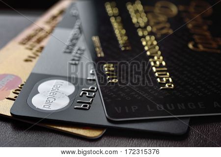 RUSSIA MOSCOW - FEB 22 2015: Premium credit card MasterCard Black Edition Gold Edition and Priority Pass access on the black leather background. Small depth of field