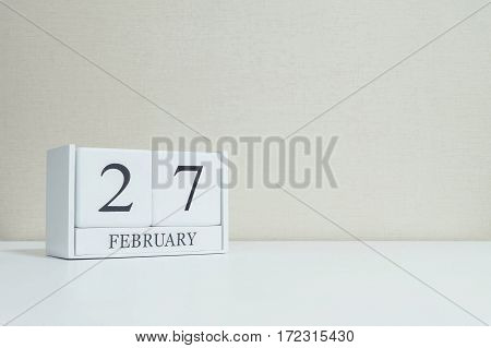 Closeup white wooden calendar with black 27 february word on blurred white wood desk and cream color wallpaper in room textured background with copy space in selective focus at the calendar
