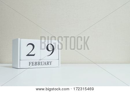 Closeup white wooden calendar with black 29 february word on blurred white wood desk and cream color wallpaper in room textured background with copy space in selective focus at the calendar