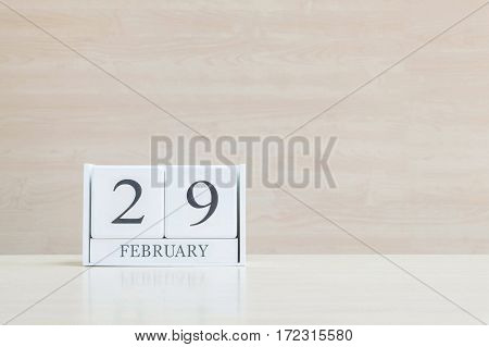 Closeup surface white wooden calendar with black 29 february word on blurred brown wood desk and wood wall textured background with copy space in selective focus at the calendar