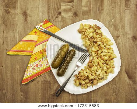 On a wooden surface is white dish with pasta fried meat and onions and pickles