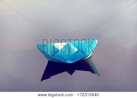 Blue paper boat floating in a pool of spring / light beam for right path