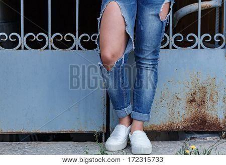 Female Legs In Torn Jeans, Close-up, Against The Background Of Openwork Lattice.