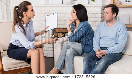 Looking for a solution. Thoughtful sad depressed woman holding her chin and listening to the psychologist while looking for a solution of her family problems