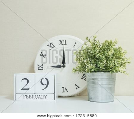White wooden calendar with black 29 february word with clock and plant on white wood desk and cream wallpaper textured background in selective focus at the calendar