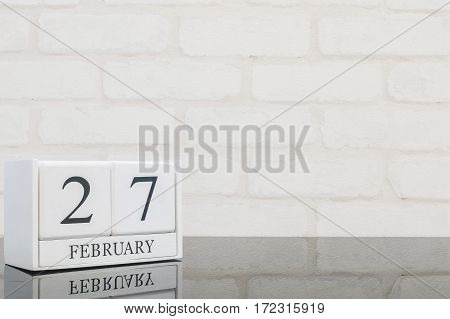 Closeup white wooden calendar with black 27 february word on black glass table and white brick wall textured background with copy space in selective focus at the calendar