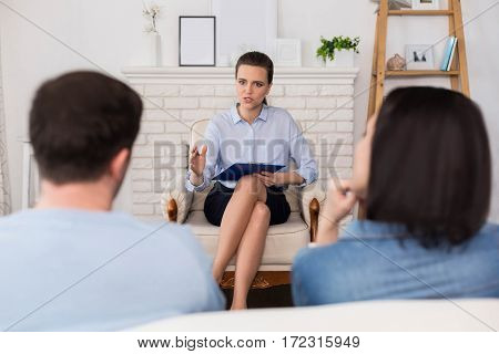 Psychological treatment. Nice young pleasant therapist sitting opposite her patients and holding her notes while interacting with them
