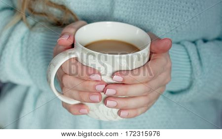 Coffee. Woman holding a cup of coffee. A woman in a knitted sweater holding a cup. Cozy.
