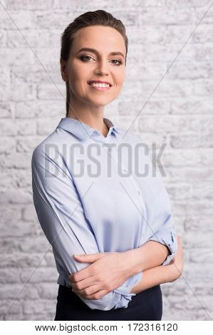 Feeling confident. Delighted cheerful attractive woman standing against the wall and smiling while feeling confident