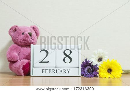 Closeup surface white wooden calendar with black 28 february word on brown wood desk and cream color wallpaper in room textured background with copy space in selective focus at the calendar