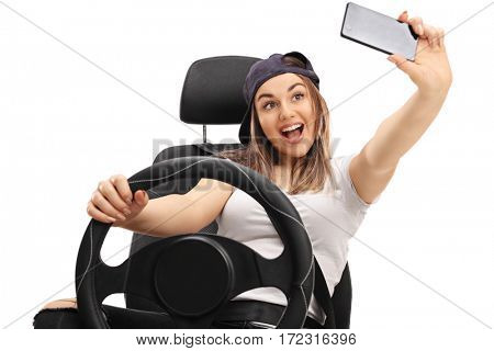 Cheerful girl sitting in a car seat and taking a selfie isolated on white background