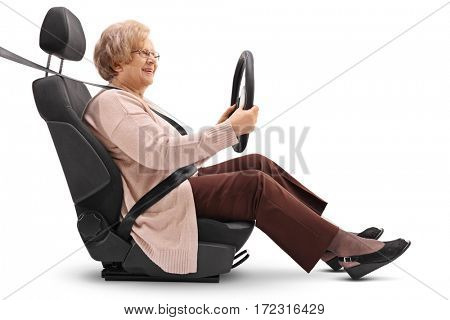 Mature woman sitting in a car seat and holding a steering wheel isolated on white background