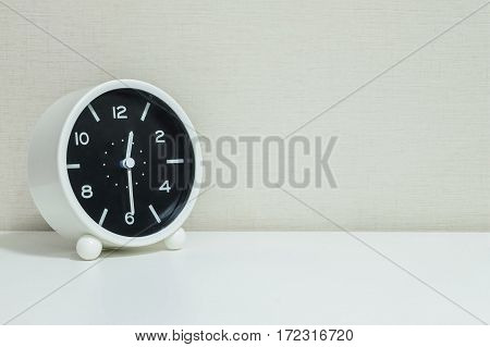 Closeup black and white alarm clock for decorate show show half past twelve or 12:30 a.m. on white wood desk and cream wallpaper textured background with copy space