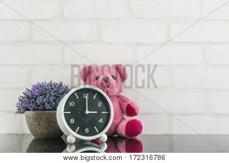 Closeup black and white alarm clock for decorate in 3 o'clock with bear doll and plant on black glass table and white brick wall textured background with copy space