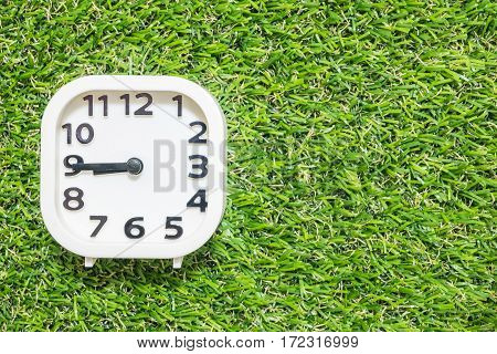 Closeup white clock for decorate show a quarter to eight or 8:45 a.m. on green artificial grass floor textured background with copy space