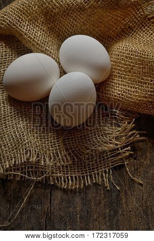 Fresh farm eggs on wooden background, close up