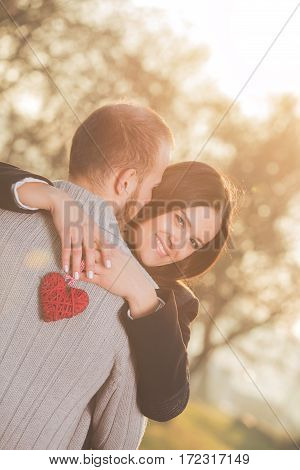 Young couple in love hugging and holding heart shape.
