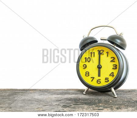 Closeup black and yellow alarm clock for decorate in 6 o'clock on old brown wood desk isolated on white background with copy space