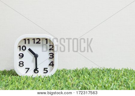 Closeup white clock for decorate show a half past ten or 10:30 a.m. on green artificial grass floor and cream wallpaper textured background with copy space