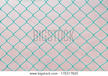 Closeup surface green steel net at the fence of tennis court textured background