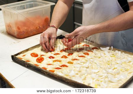 Baker Putting Ingredients On Focaccia