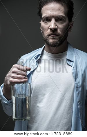 Have problems. Frowning man looking angrily on camera wearing blue shirt over white T-shirt posing with glass bottle of alcohol, isolated on grey background