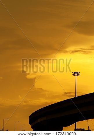Silhouette of elevated roads with electricity post in the gold sunset sky background.