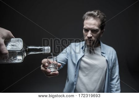 Give your cup. Close up of bottle with beverage being situated in male hand pouring alcohol into small glass, isolated on grey background