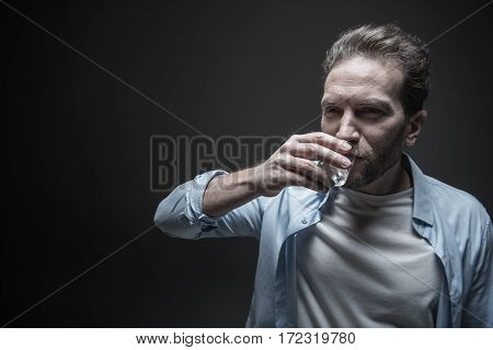 For your health. Satisfied man wearing blue shirt over white T-shirt keeping small glass in right hand near his mouth while looking aside
