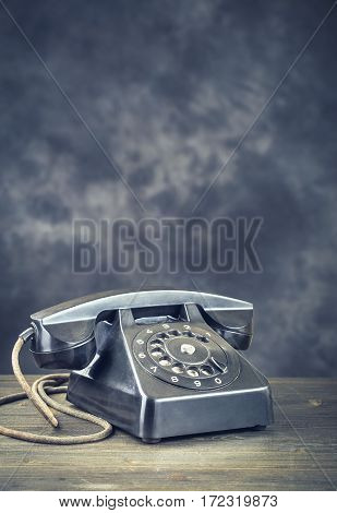 Old black phone on wooden table with copy space on dark abstract background