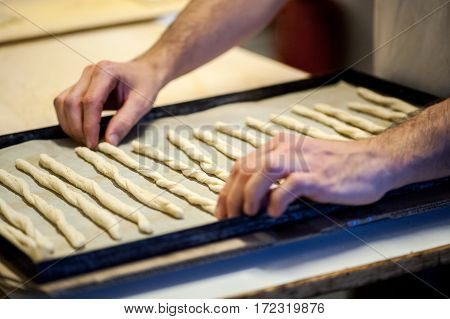 Baker Placing Breadsticks On Baking Tray