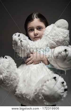 I am afraid. Little scared girl with widely opened eyes looking straight at camera while hiding herself behind big toy standing over grey background