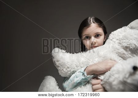 Do not hurt me. Frightened girl looking straight at camera while embracing white big bear, standing over grey background