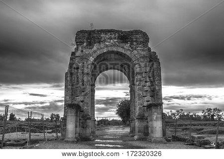 Roman Arch of Caparra at dusk. B&W Shot. Crossroad ancient city ruins at Silver Route Via de la Plata Caceres Spain