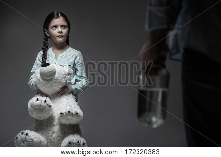 Family grief. Frightened girl pressing her lips while looking at male person with bottle in hand, holding big white bear