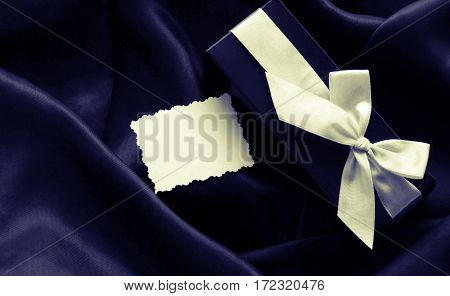 chic holiday gift box with a white ribbon and vintage paper on black silk fabric toned top view