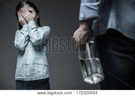 Stop it. Serious little lady wearing jeans skirt and striped shirt keeping her hands on eyes standing over grey background
