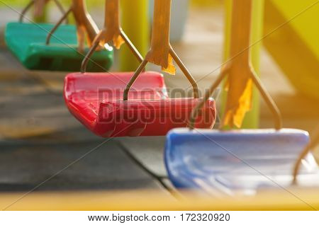 Empty blue red green plastic swing at children playground.