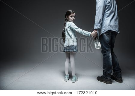 Hi is my father. Serious very young lady wearing casual clothes having two long braids putting her hand on the hand of her father, isolated on grey